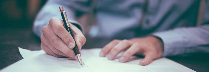 Photo of a person holding a pen signing their Will